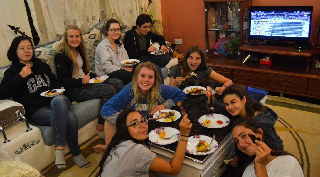 Volunteers eat together in their shared accommodation after a day of hard work